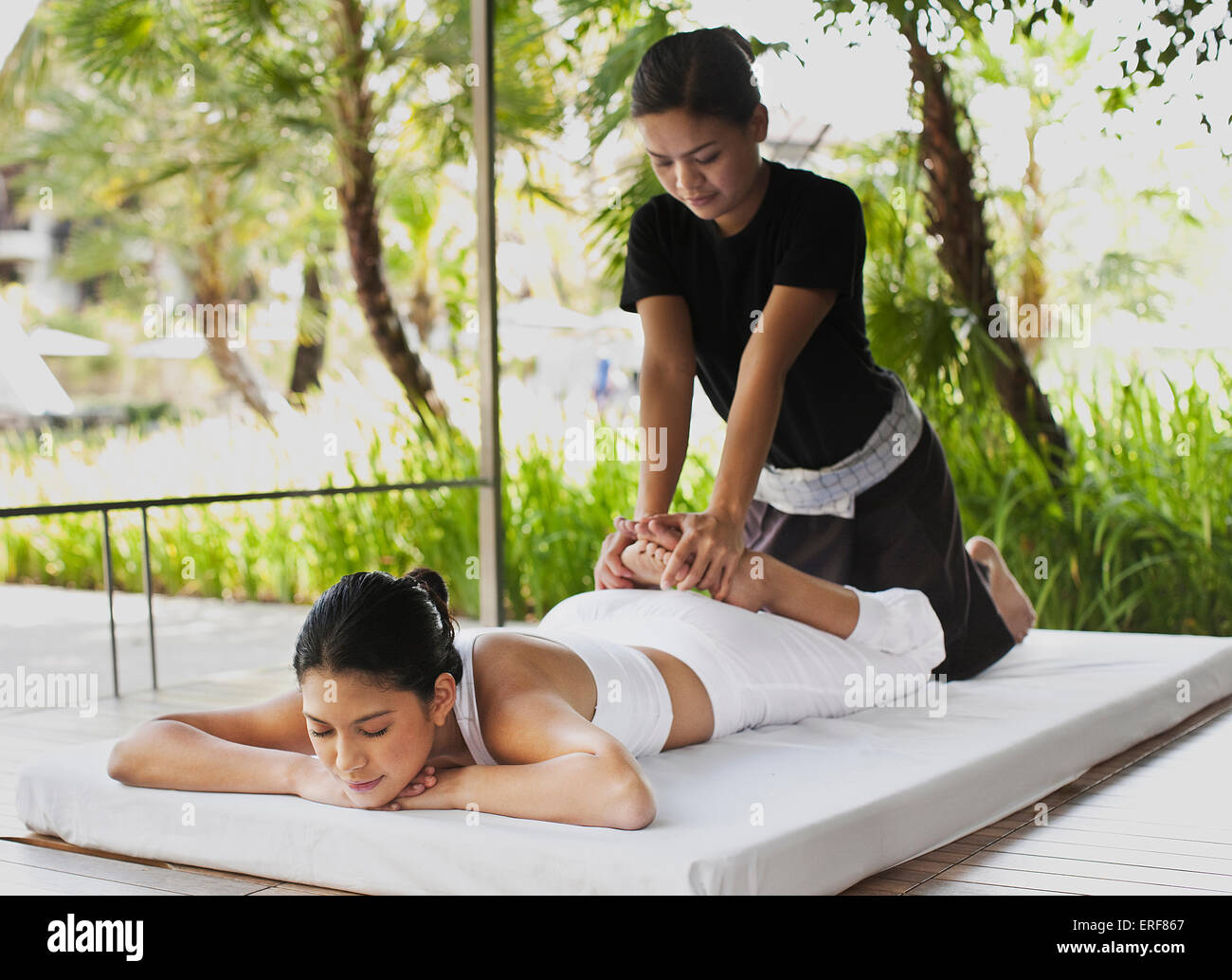A woman receives a Thai Massage in an outdoor cabana by the main pool. - Stock Image