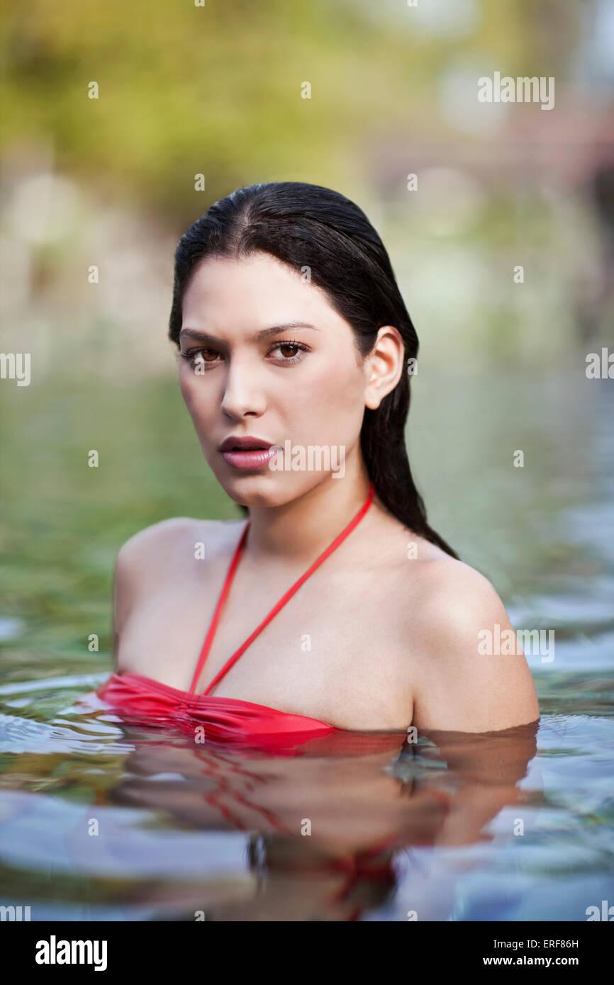 Woman Swimming in Pool at Indigo Pearl, Phuket, Thailand. A woman swims in the main pool at Indigo Pearl resort. - Stock Image