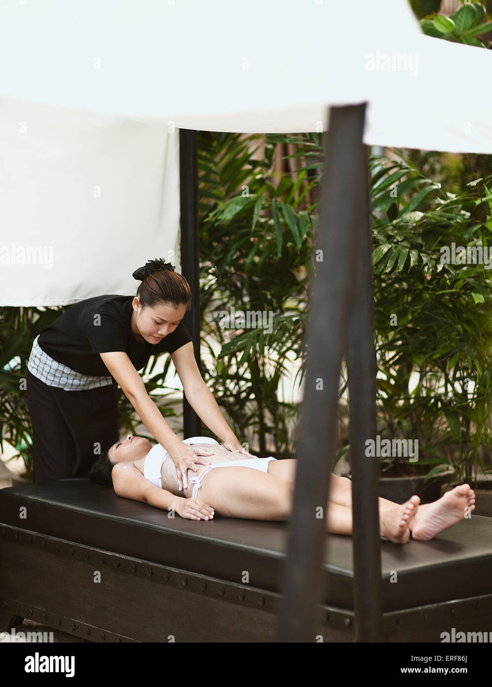 Woman Receiving Body Scrub at Indigo Pearl, Phuket, Thailand. A woman receives a Thai Rice Scrub at on outdoor beach - Stock Image