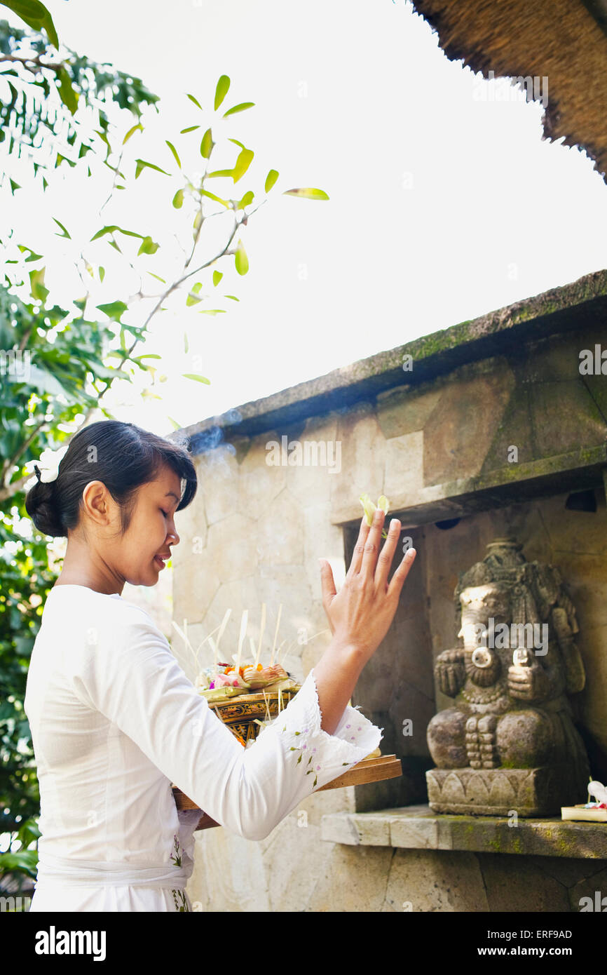 Balinese woman making morning offering to the Hindu God Ganesh outside Room #14  at Ubud Hanging Gardens, Bali, - Stock Image