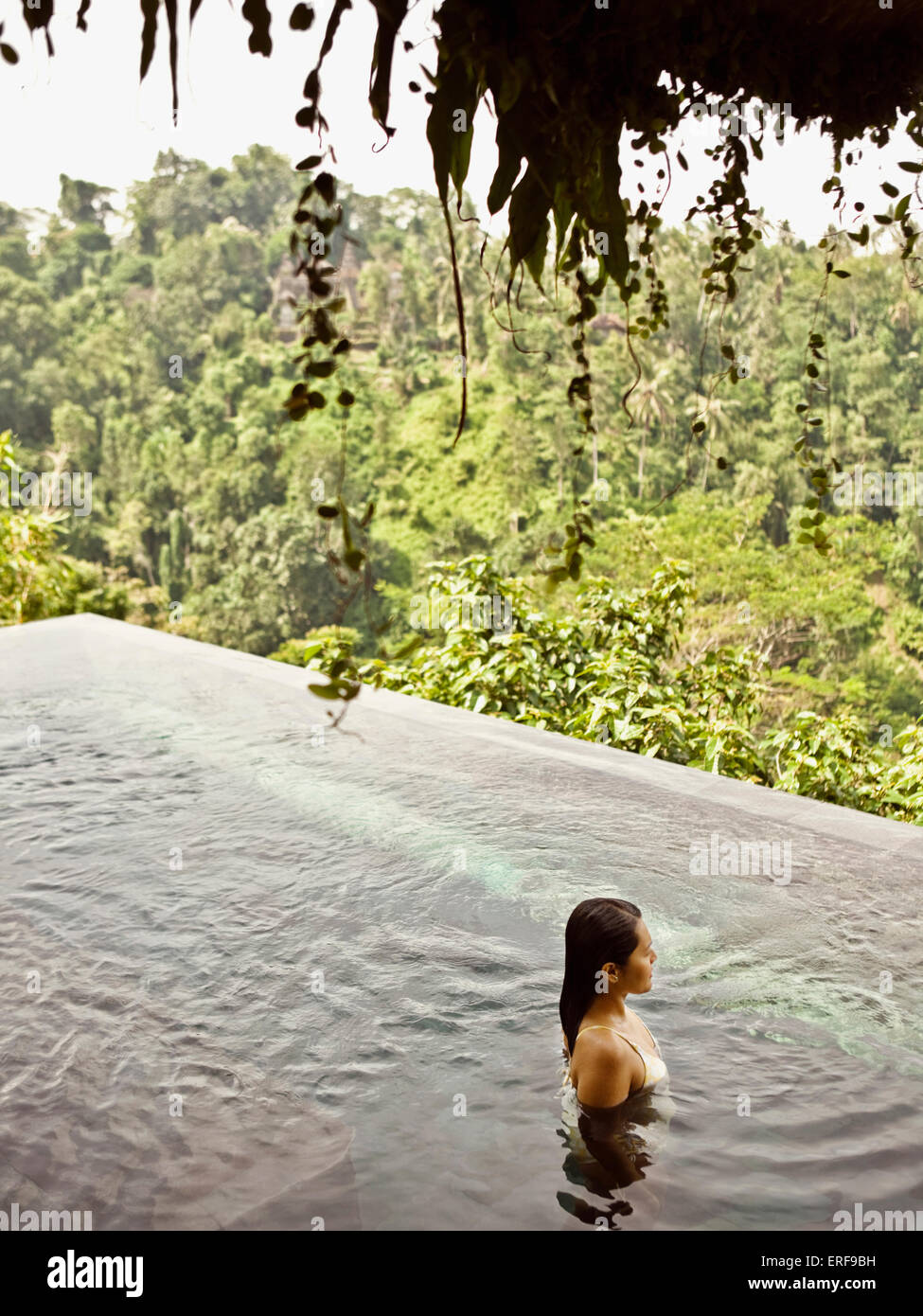 Asian female guest in infinity pool of private pool villa at Ubud Hanging Gardens, Bali, Indonesia. - Stock Image