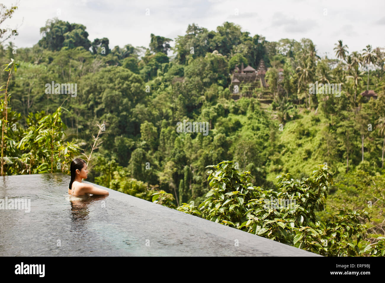 Asian female guest in infinity pool of private pool villa at Ubud Hanging Gardens, Bali, Indonesia. The infinity - Stock Image