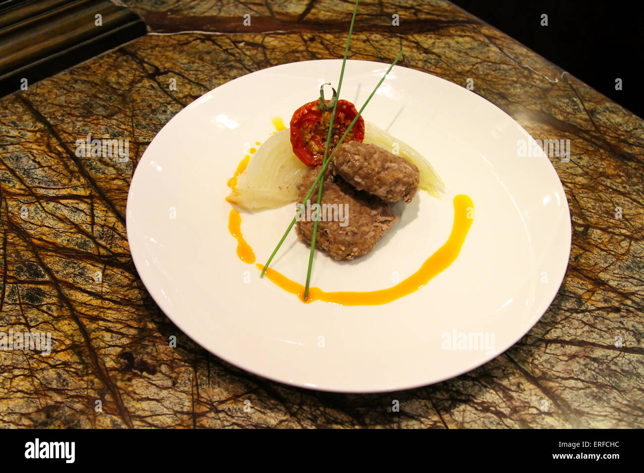 Delicious appetiser with some meat served in a white plate. - Stock Image