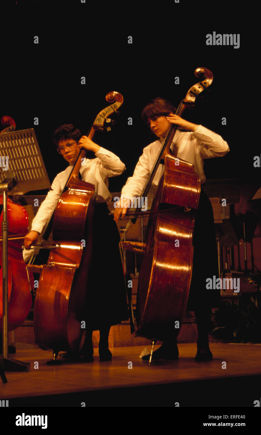 Double bass played by two girls - Stock Image
