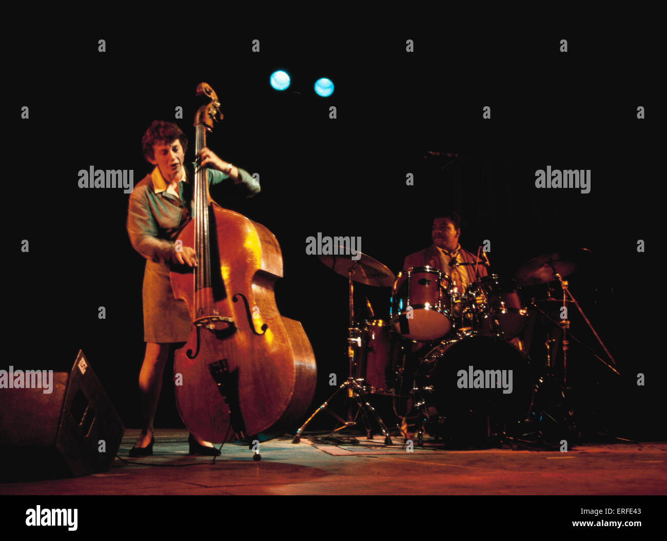 Double bass played pizzicato (plucked) - Jazz setting. Drum kit in background - Stock Image