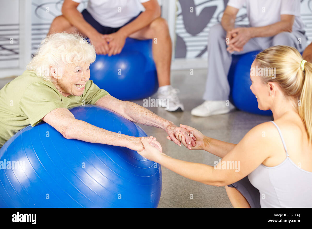 Happy senior woman with fitness instructor in rehab center - Stock Image
