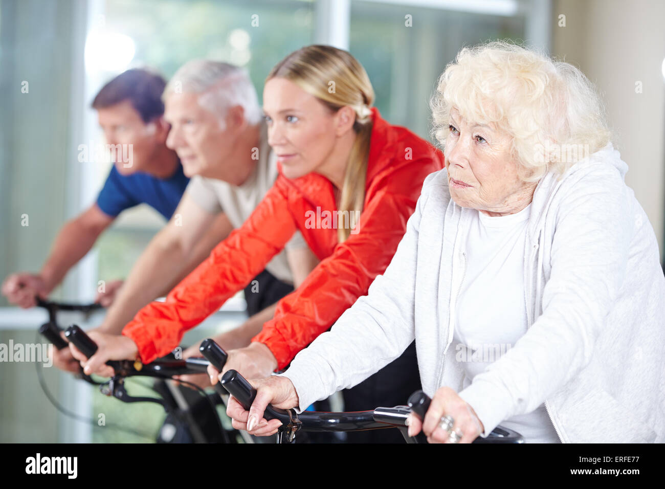 Senior group together in a spinning class in rehab care center - Stock Image