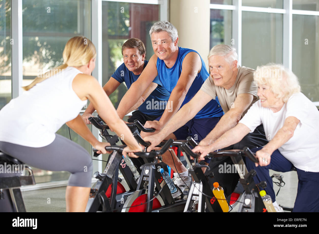Senior people with trainer in gym exercising on spinning bikes - Stock Image
