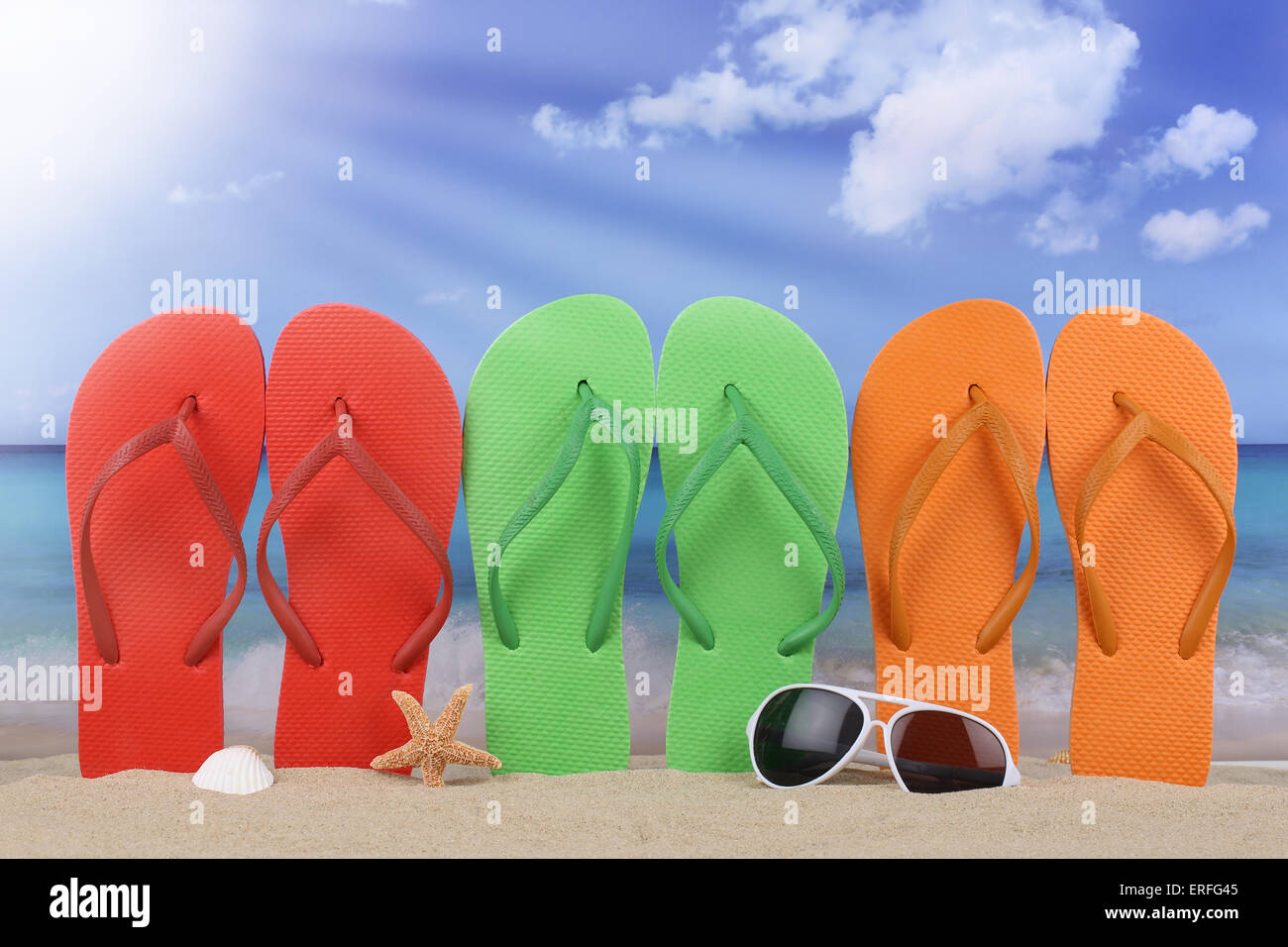 Beach scene with flip flops sandals in summer on vacation, holidays - Stock Image