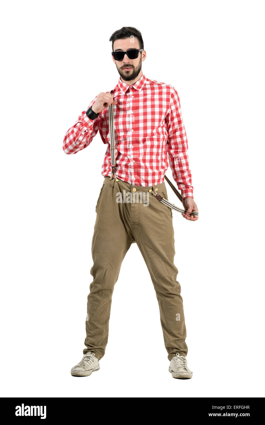 Cool young bearded hipster putting on suspenders. Full body length portrait isolated over white background. - Stock Image