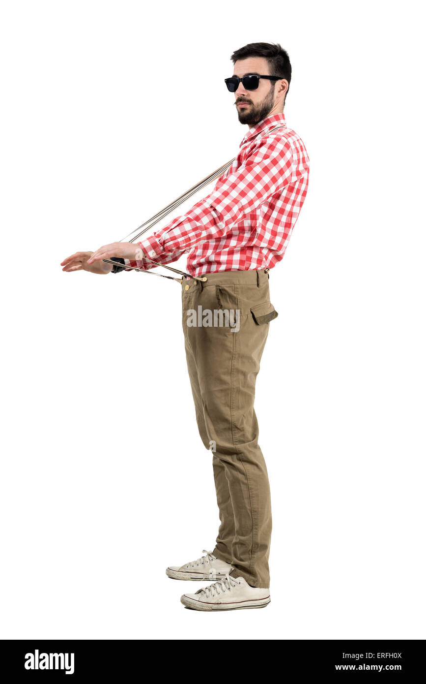 Eccentric hipster stretching suspenders looking at distance. Full body length portrait isolated over white background. - Stock Image