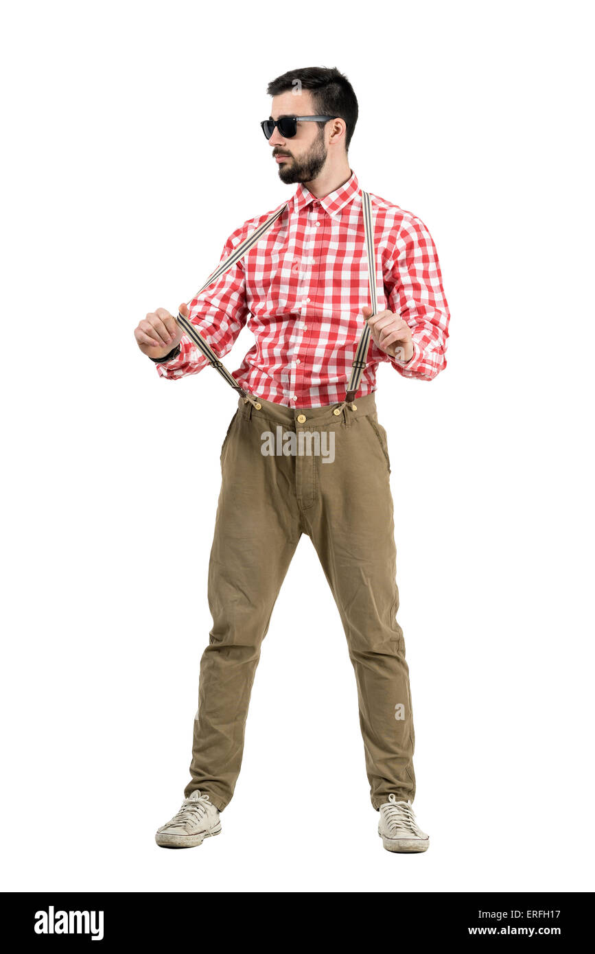 Young bearded hipster pulling suspenders looking away. Full body length portrait isolated over white background. - Stock Image