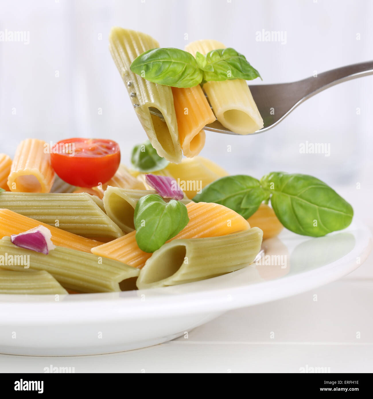 Italian cuisine eating colorful Penne Rigate noodles pasta meal with fork - Stock Image