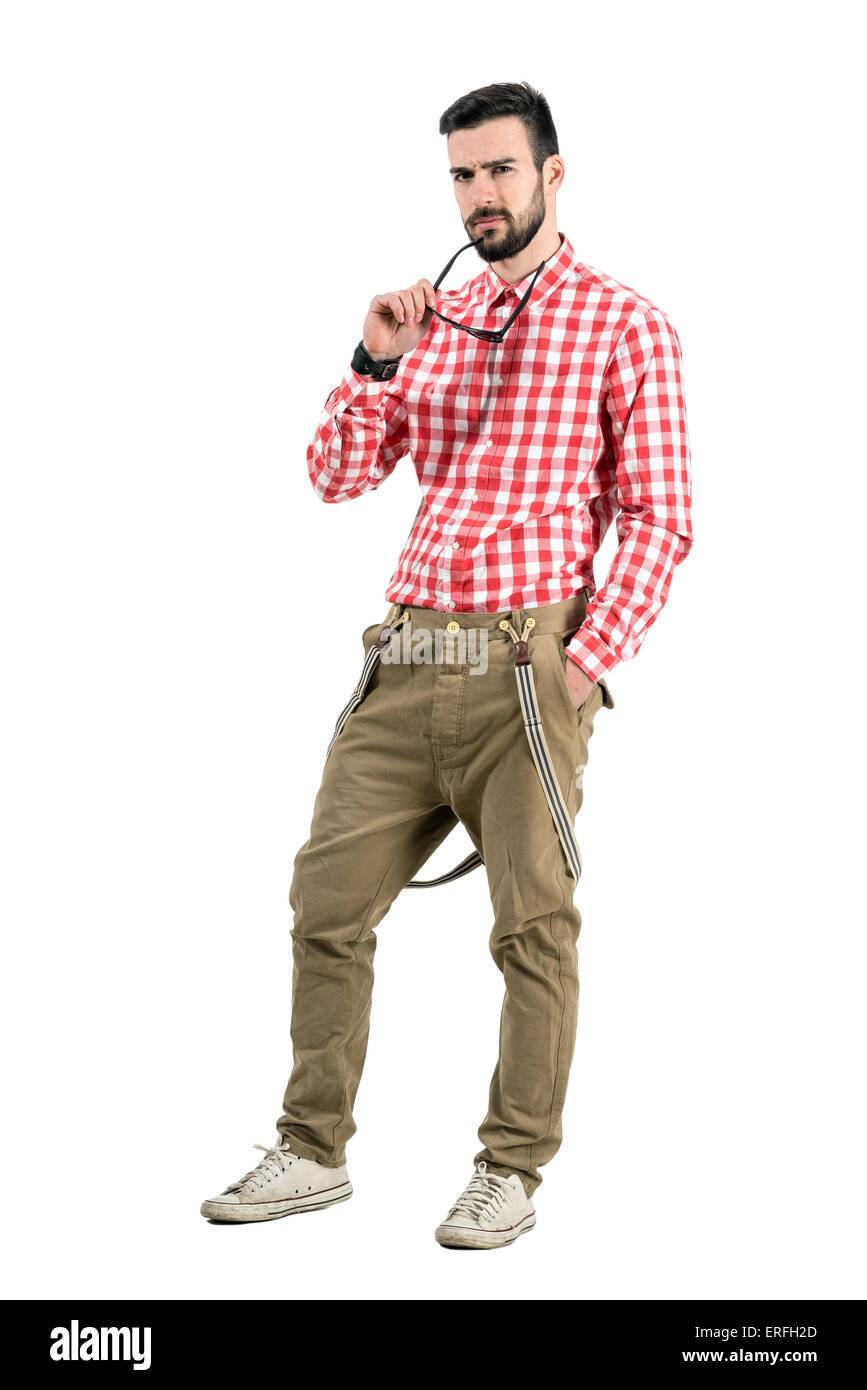 Young hipster holding sunglasses with distrustful look at camera. Full body length portrait isolated over white - Stock Image