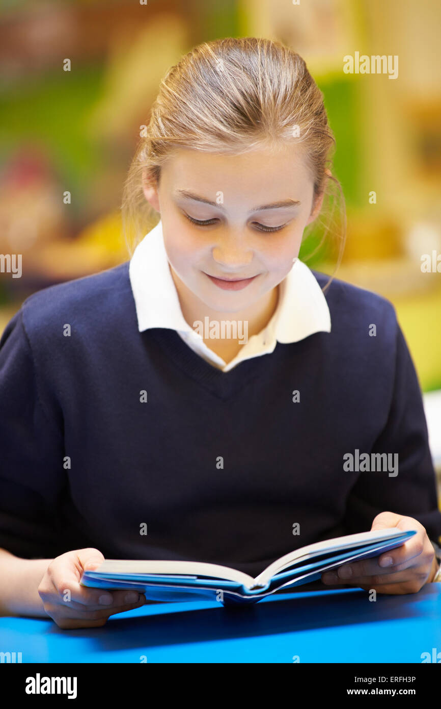 Female Elementary School Pupil Reading Book In Classroom - Stock Image