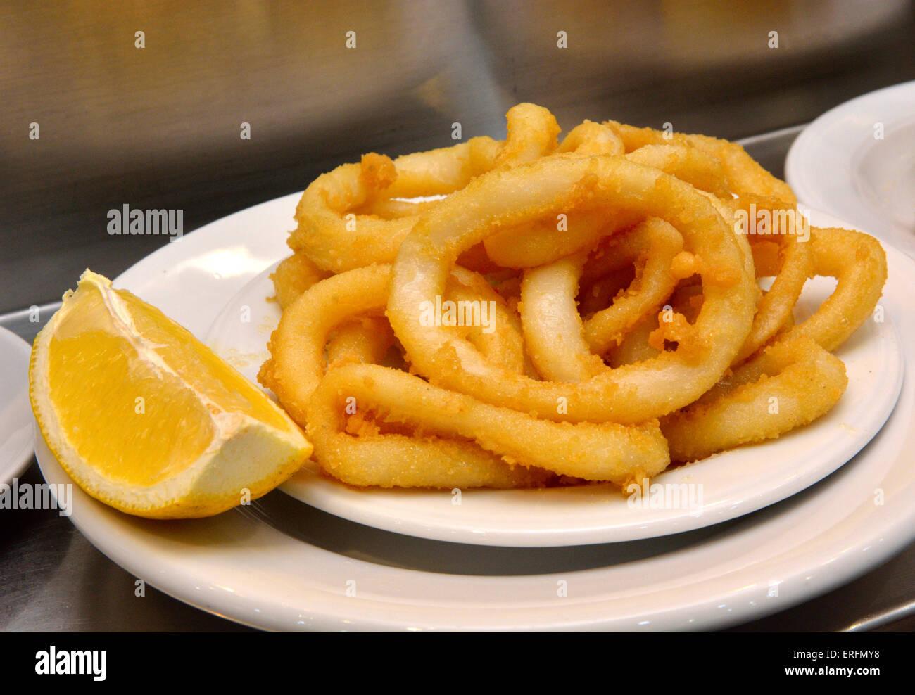 Plate of calamari with lemon - Stock Image