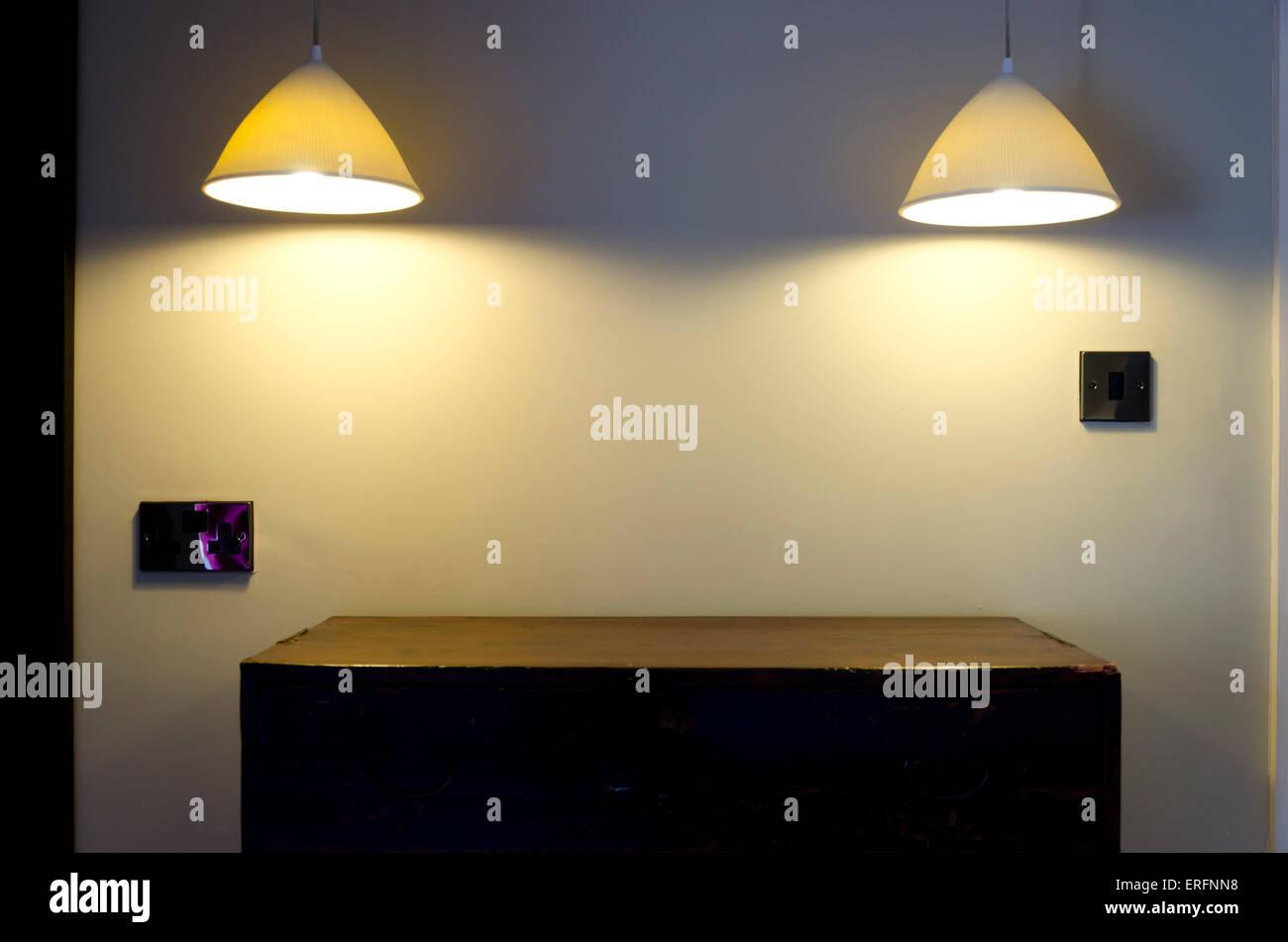 Lamps illuminating empty sideboard. - Stock Image