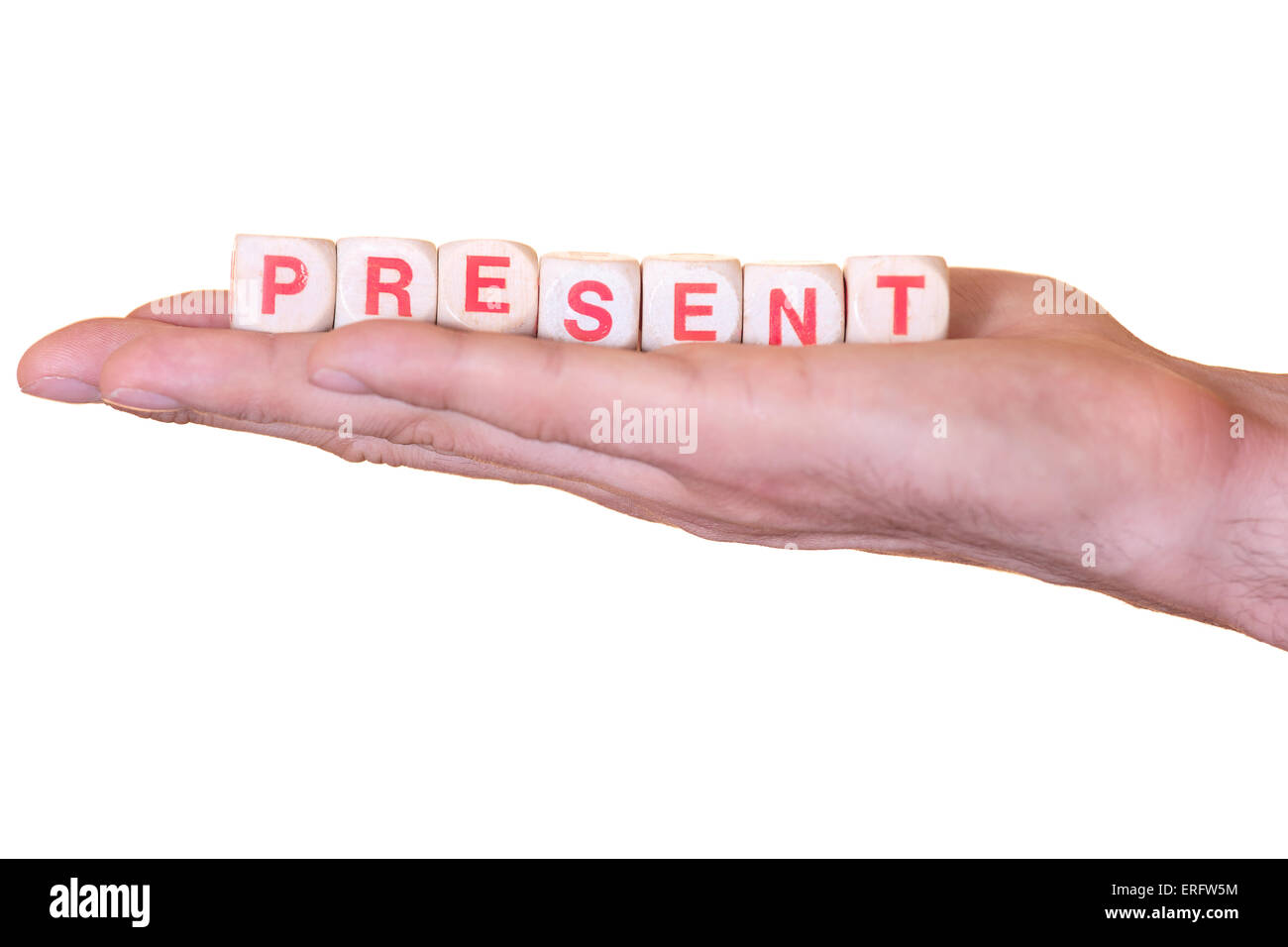 The word present written with wooden dice on the he palm of the hand. Isolated on white background - Stock Image