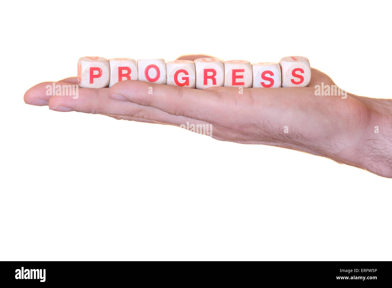 The word progress written with wooden dice on the he palm of the hand. Isolated on white background - Stock Image