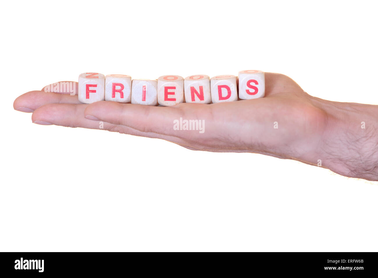 The word friends written with wooden dice on the he palm of the hand. Isolated on white background - Stock Image