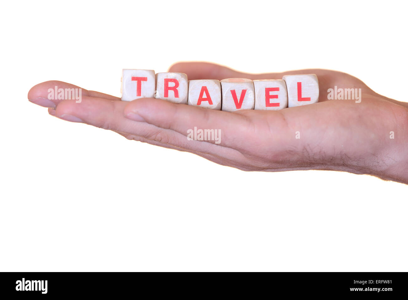 The word travel written with wooden dice on the he palm of the hand. Isolated on white background - Stock Image