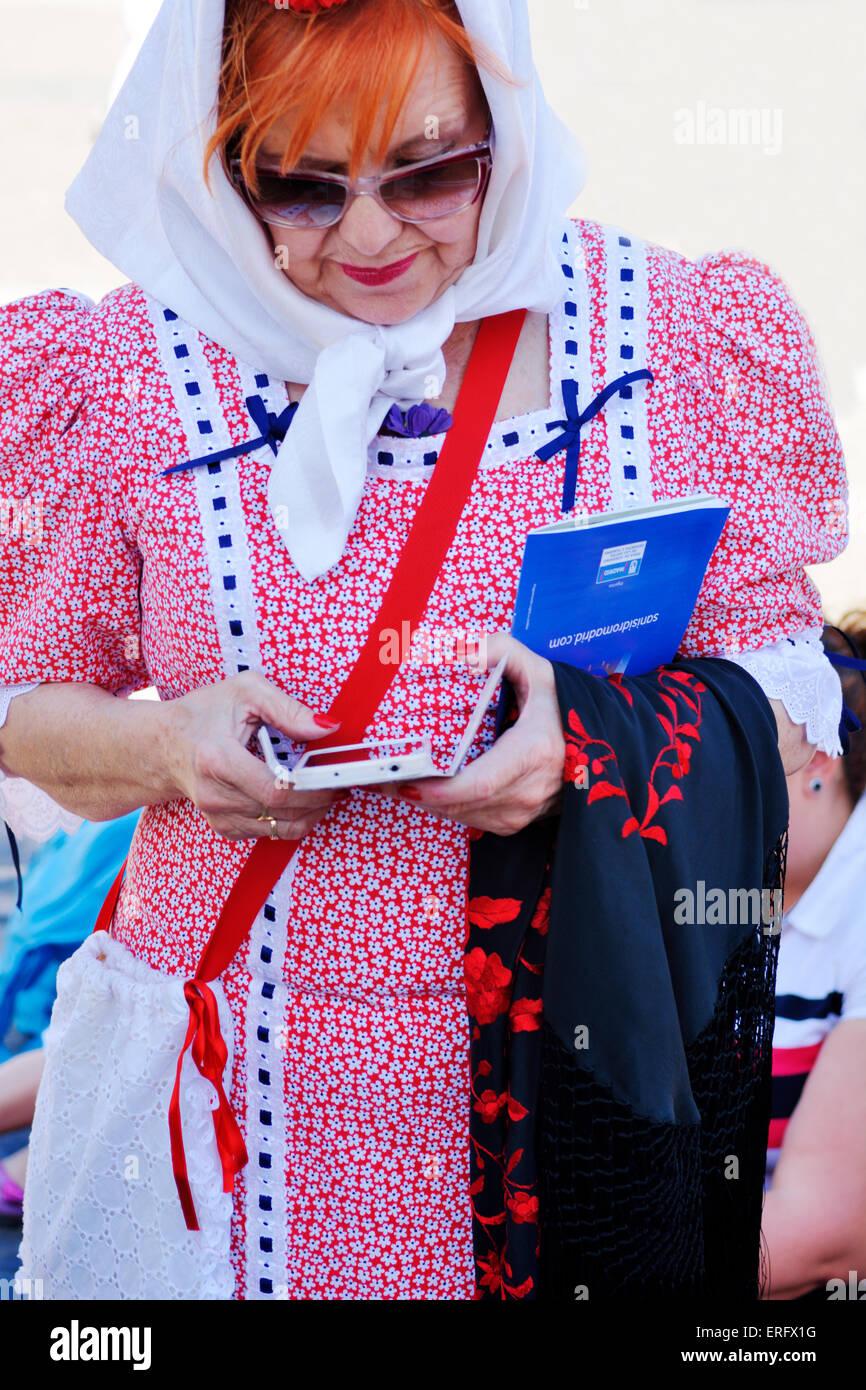 Traditionally dressed Spanish woman using smart phone - Stock Image