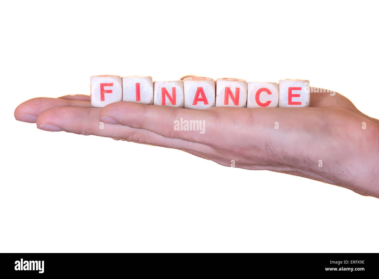 The word finance written with wooden dice on the he palm of the hand. Isolated on white background - Stock Image