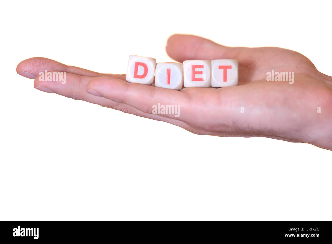 The word diet written with wooden dice on the he palm of the hand. Isolated on white background - Stock Image