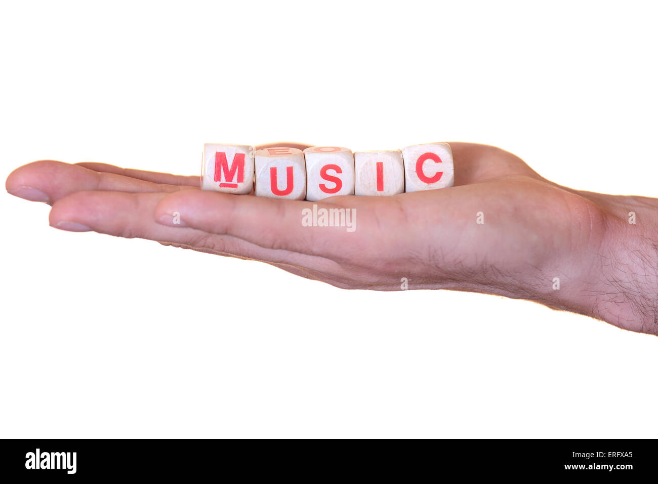 The word music written with wooden dice on the he palm of the hand. Isolated on white background - Stock Image