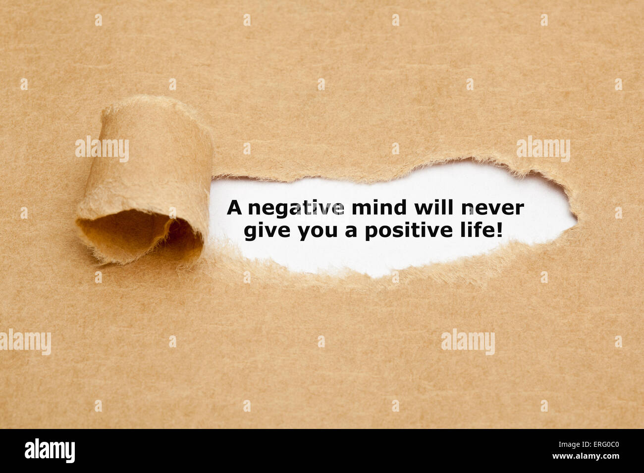 The text A negative mind will never give you a positive life, appearing behind torn brown paper. - Stock Image