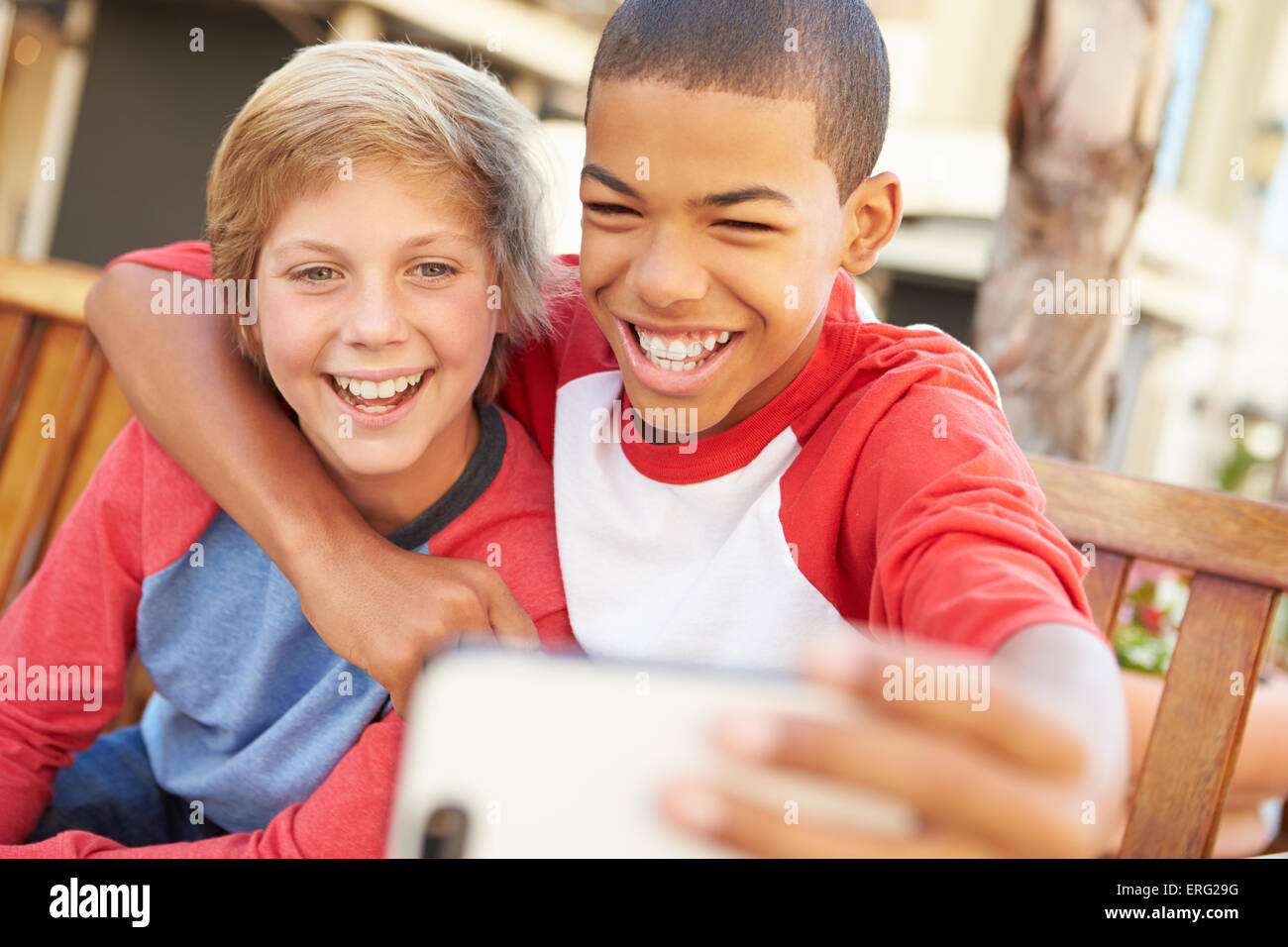 Two Boys Sitting On Bench In Mall Taking Selfie - Stock Image