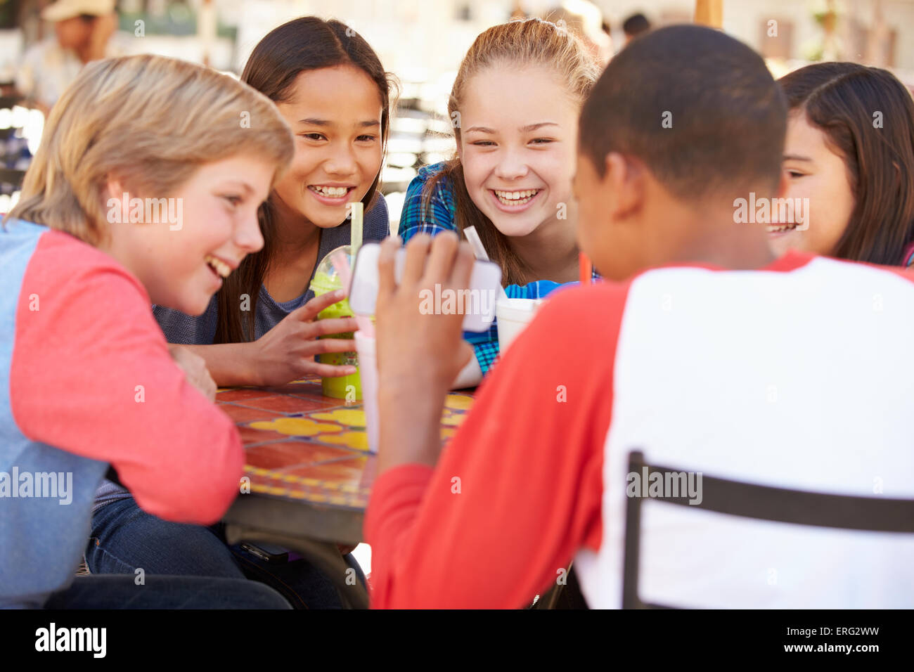 Group Of Children In CafŽ Looking At Text On Mobile Phone - Stock Image