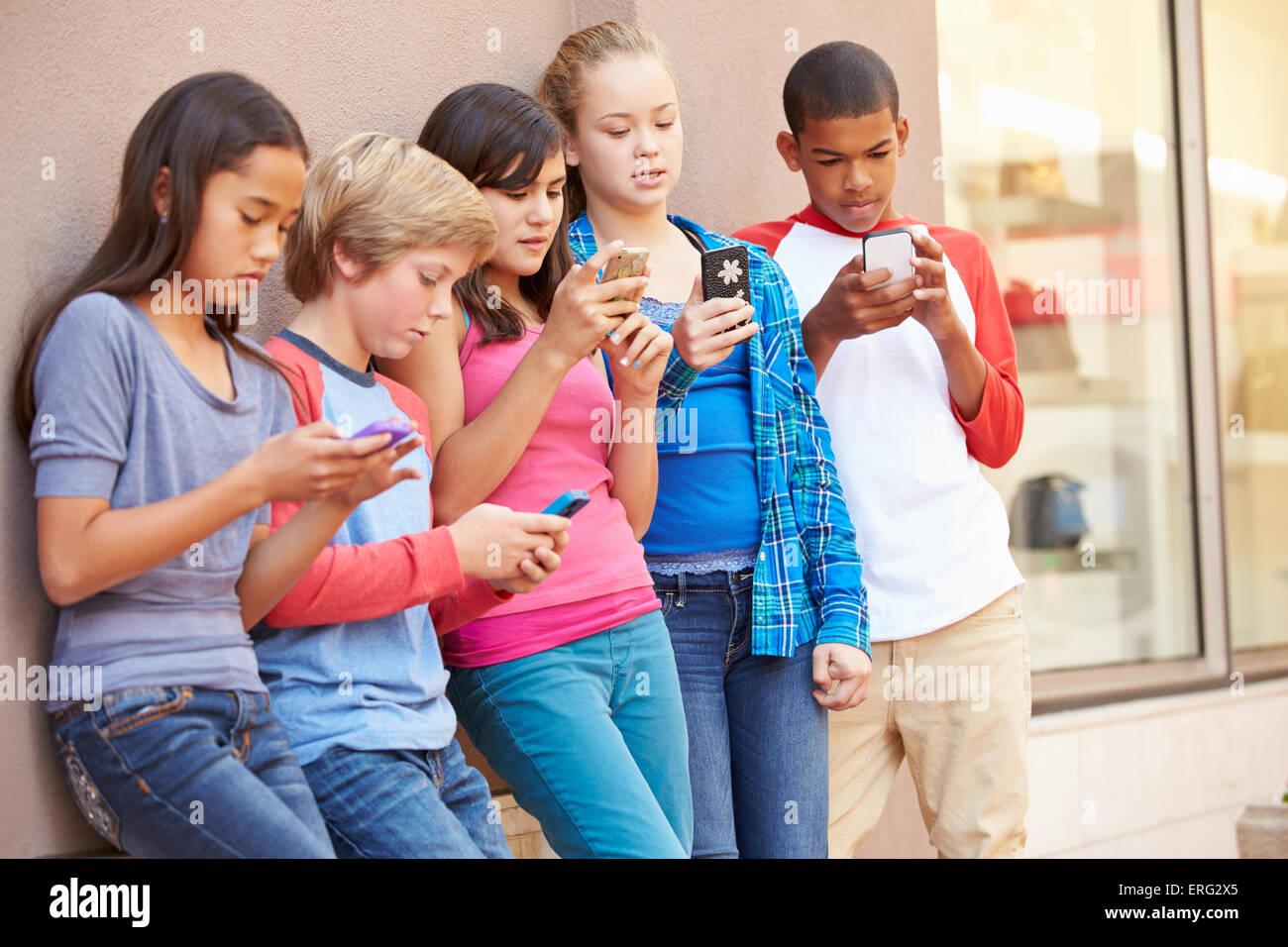 Group Of Children Sitting In Mall Using Mobile Phones - Stock Image