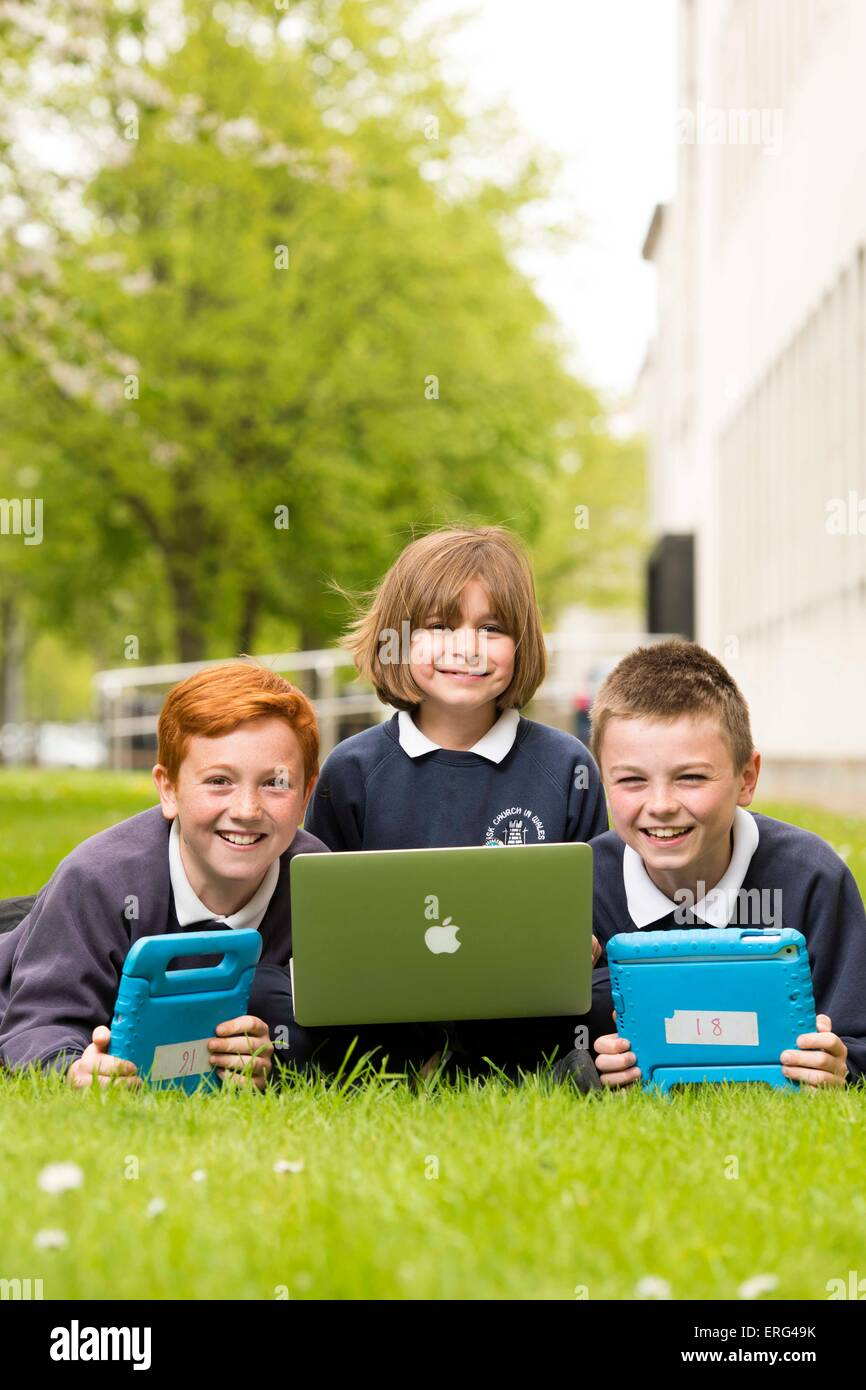 School children learning about technology and computers while outside using laptops. - Stock Image