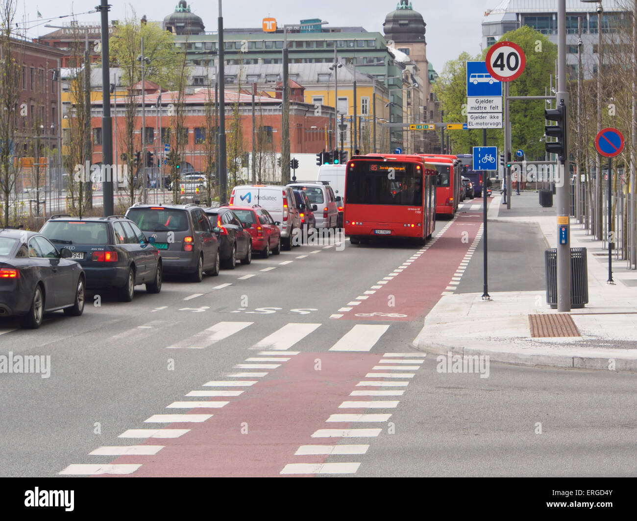 Downtown Oslo Norway, prioritized bike lane with red tarmac and bus lane, congested ordinary traffic lane - Stock Image