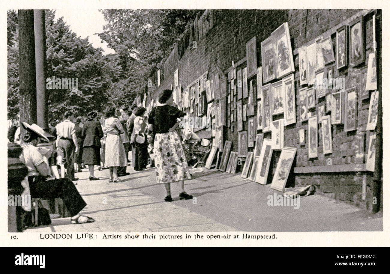 Pictures shown in the open-air at Hampstead Heath. London. Passersby browse the pictures hanging on the walls. - Stock Image