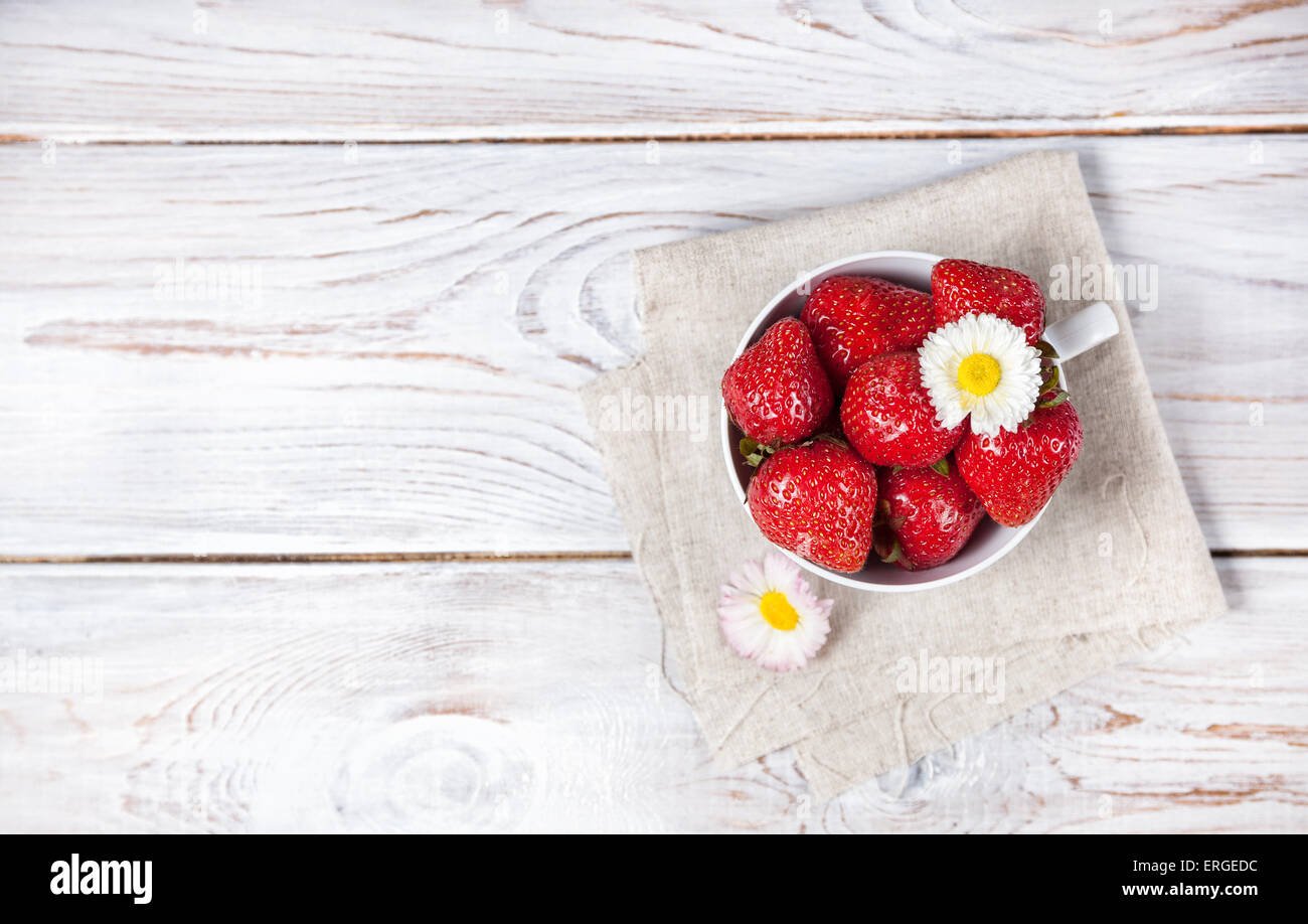 Strawberry in the cup with white flower on wooden table - Stock Image
