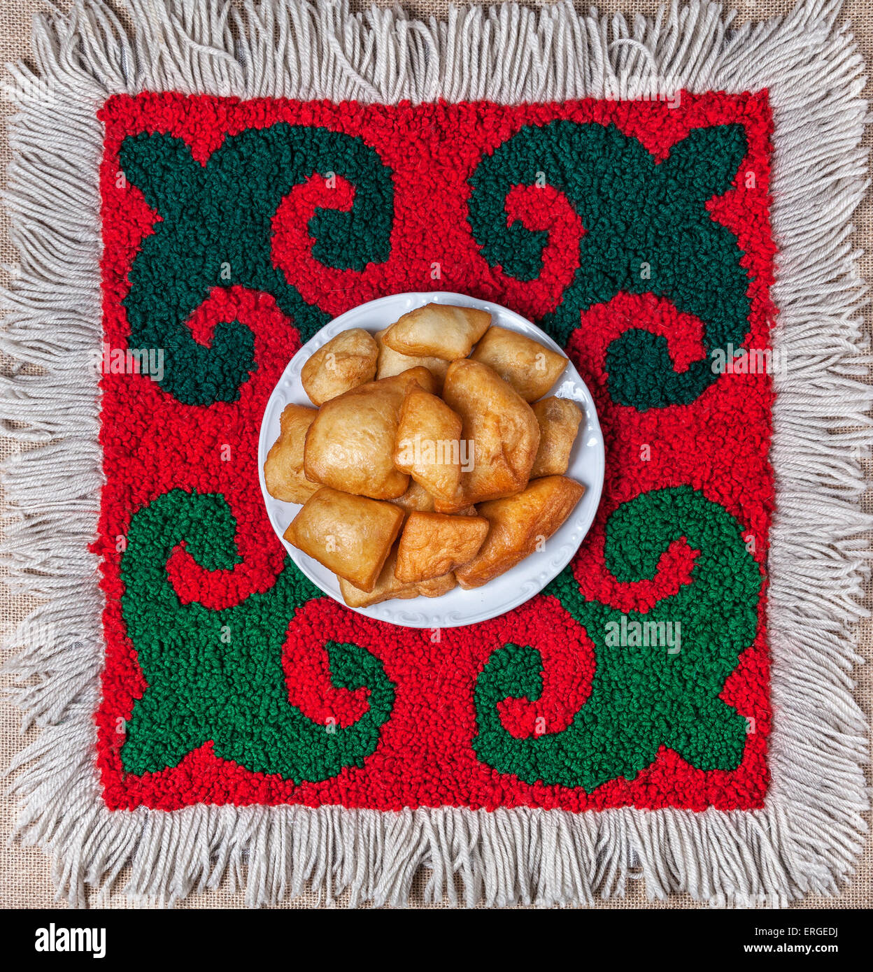 Kazakh national food baursak bread on the ethnic red carpet with oriental green pattern - Stock Image
