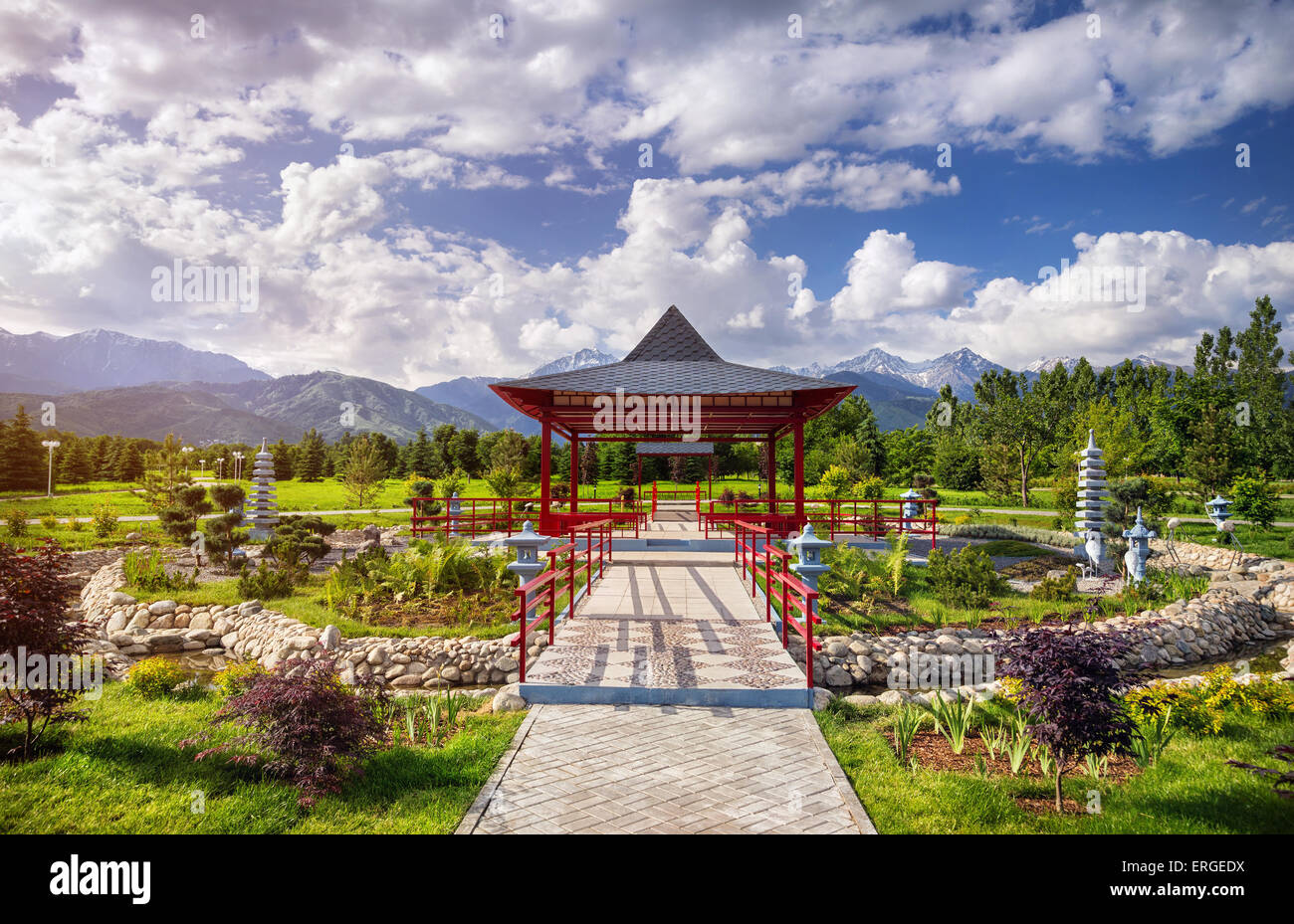 Japanese garden with red pagoda at mountains and blue sky in dendra park of first president in Almaty, Kazakhstan - Stock Image