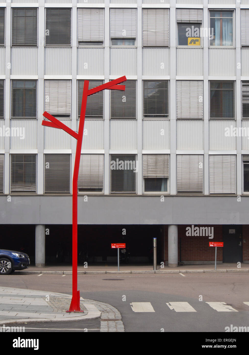 Single red painted steel lamppost in an artsy industrial style set against a gray office block in Kvaernerbyen, - Stock Image