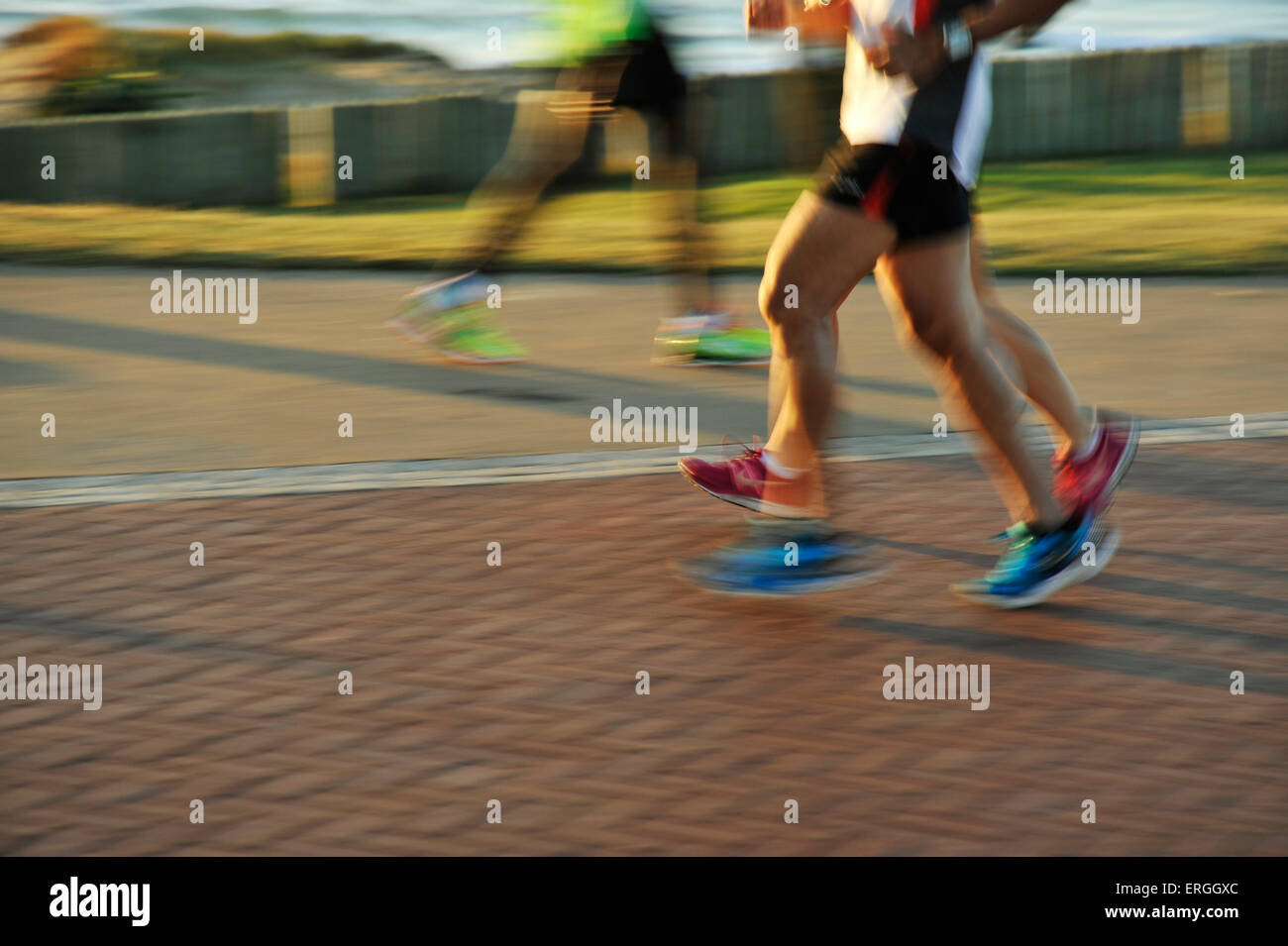 Muscular legs and feet of athletic adult men and woman runners taking early morning exercise on beachfront - Stock Image