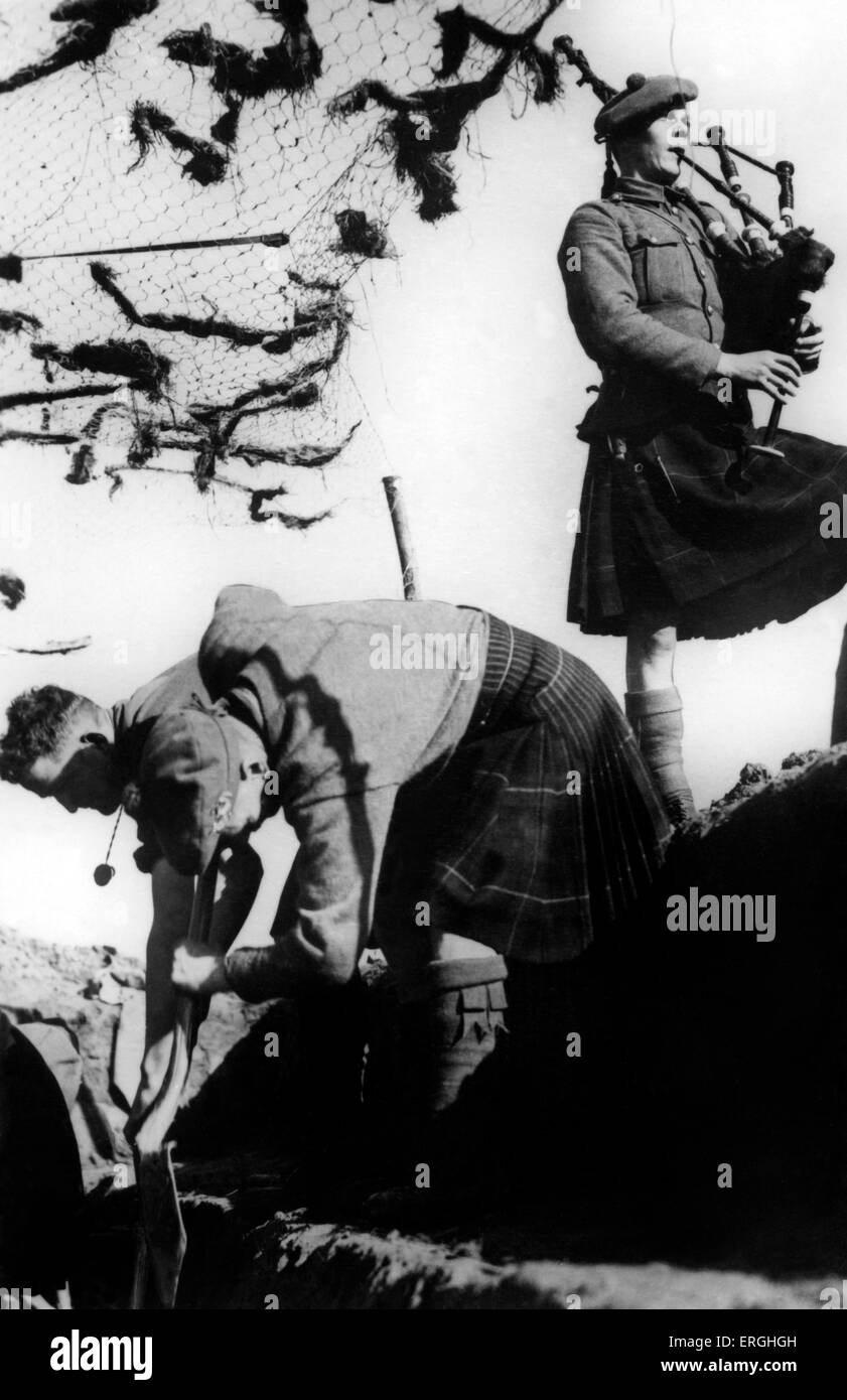 World War 2: Highlanders begin digging a trench, accompanised by a bagpiper. Caption: A detatchment of a Highland - Stock Image