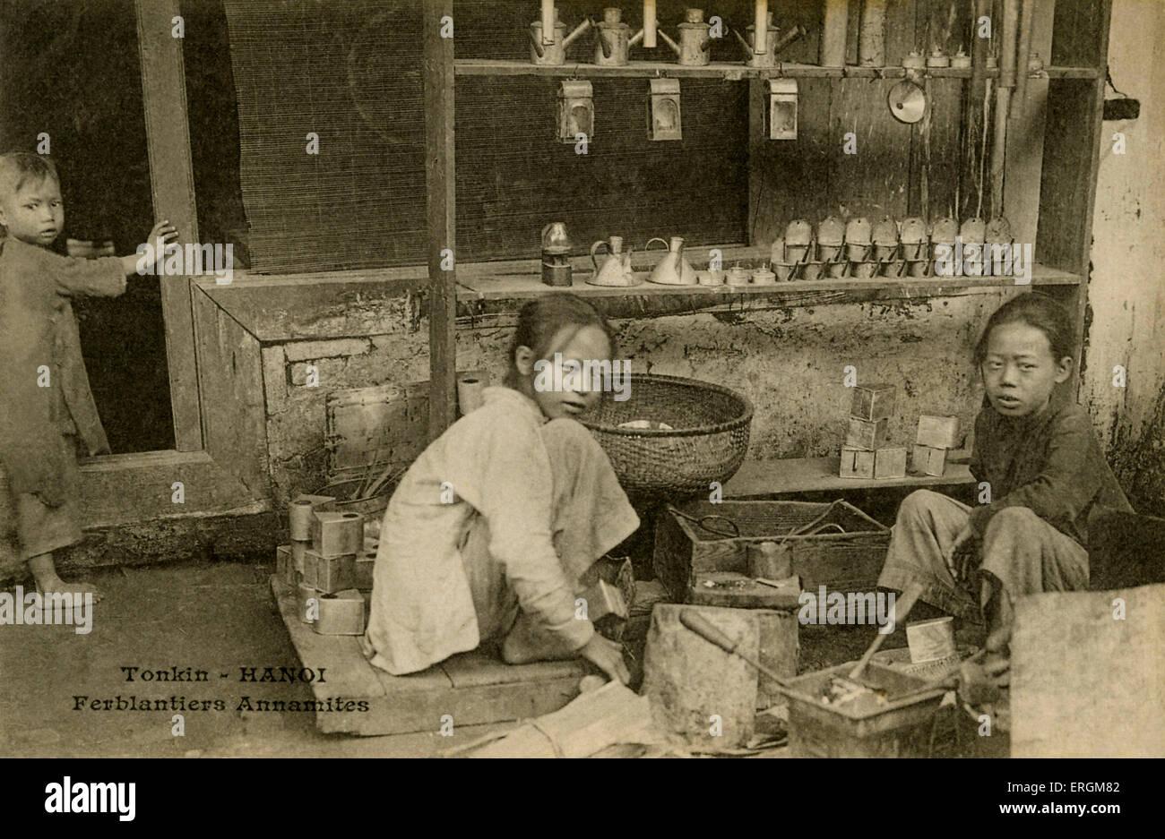 Child tinplate workes/ tinkers/  tinsmiths, Hanoi, Tonkin, north Vietnam. Postcard after photograph, 20th century. - Stock Image