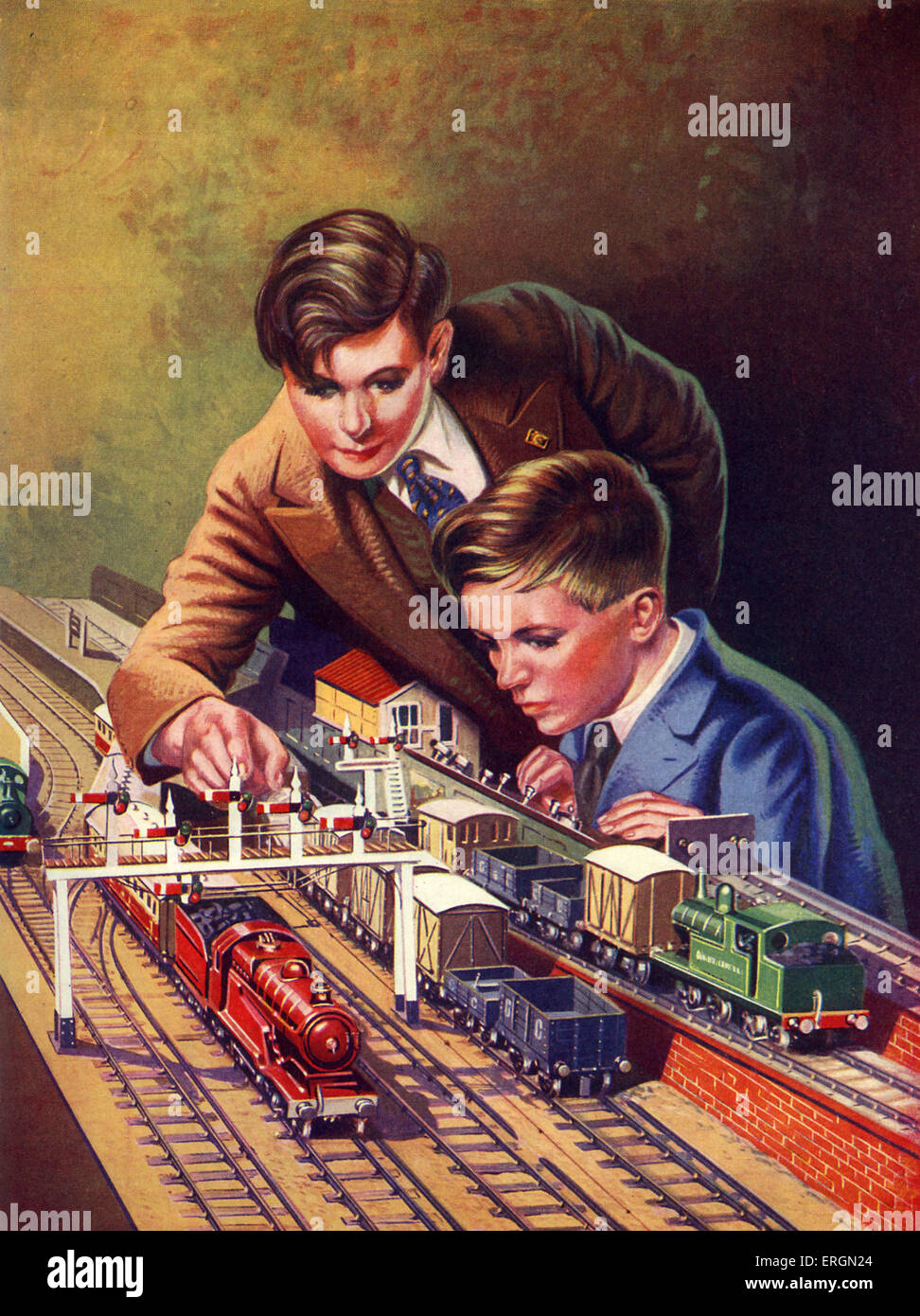 Two boys working their model railway.  Modle trains pulling trucks with coal and a signalling system. C. 1938. Artist - Stock Image