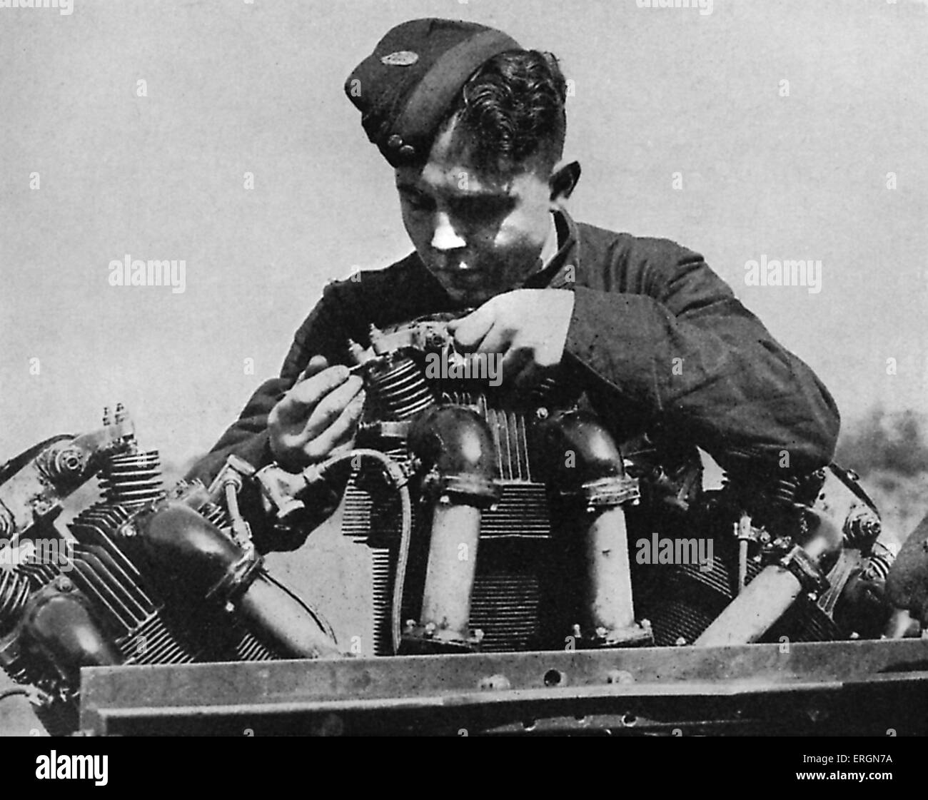 WW2 - RAF apprentice mechanic at work on the ground. Caption reads: A boy trainee assembling an aeroplane engine - Stock Image