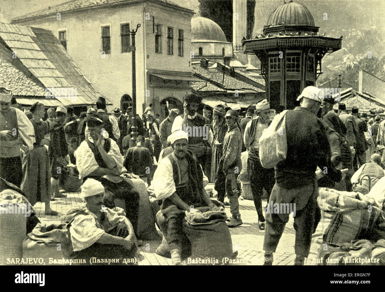 Tthe market in Sarajevo, Serbia. C. 1930s. Men wearing traditional costume with large sacks of produce. One woman - Stock Image