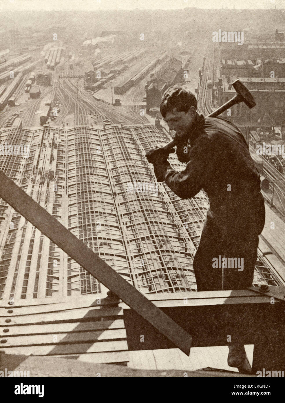 Worker on scaffold -Caption reads 'At work on the frame of a lofty modern building.' - Stock Image