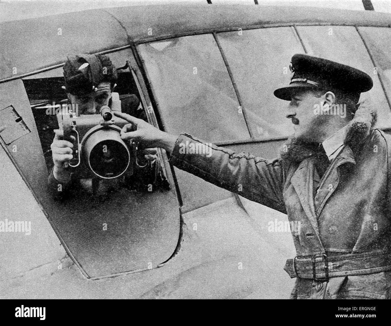 WW2 - Aerial Reconnaissance. Man being instructed how to use an aerial camera on a plane. - Stock Image
