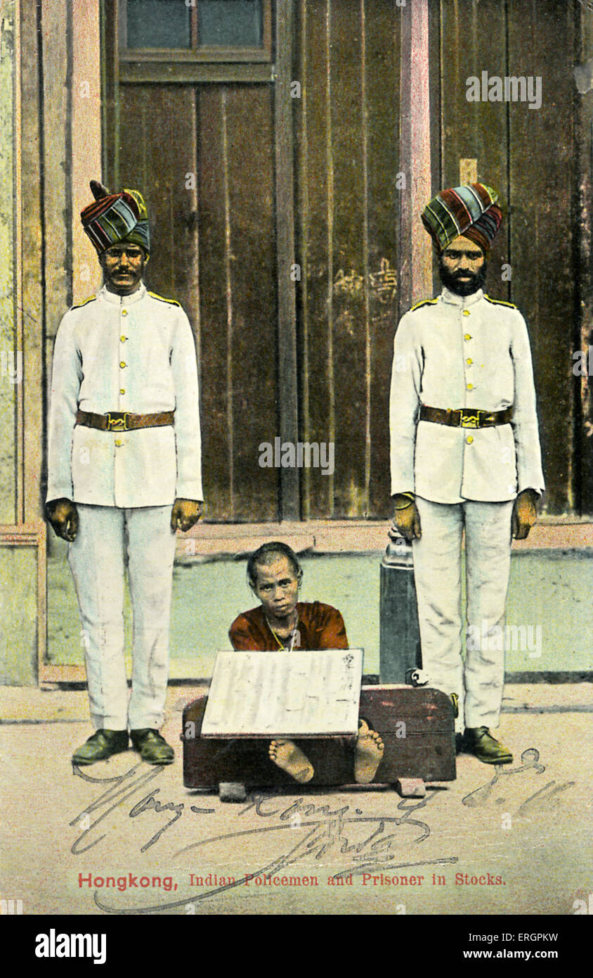 Indian policemen of the Hong Kong police force stand either side of a Chinese prisoner in stocks. Early 20th century. - Stock Image