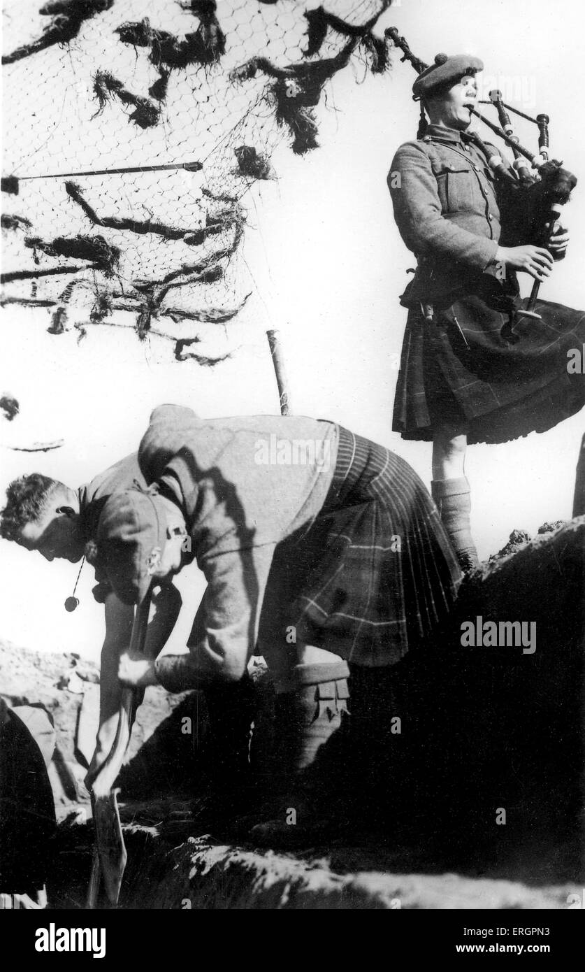 WWII - Scottish soldiers. Two men dig a trench accompanied by another playing bagpipes. Caption reads: 'A detachment - Stock Image